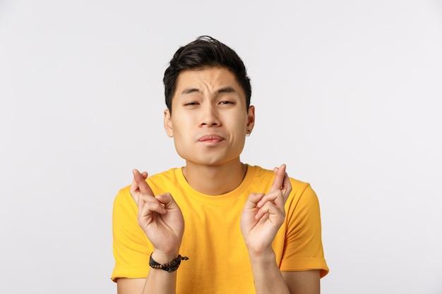 Leuke aziatische mens die in gele t-shirt vingers kruisen voor geluk Premium Foto
