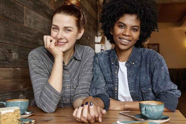 Leuke blanke vrouw met haarbroodje die hand van haar stijlvolle afrikaanse vriendin tijdens de lunch Gratis Foto