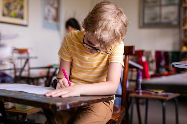 Leuke blonde schoolstudent die met modieuze glazen in klaslokaal schrijven Premium Foto
