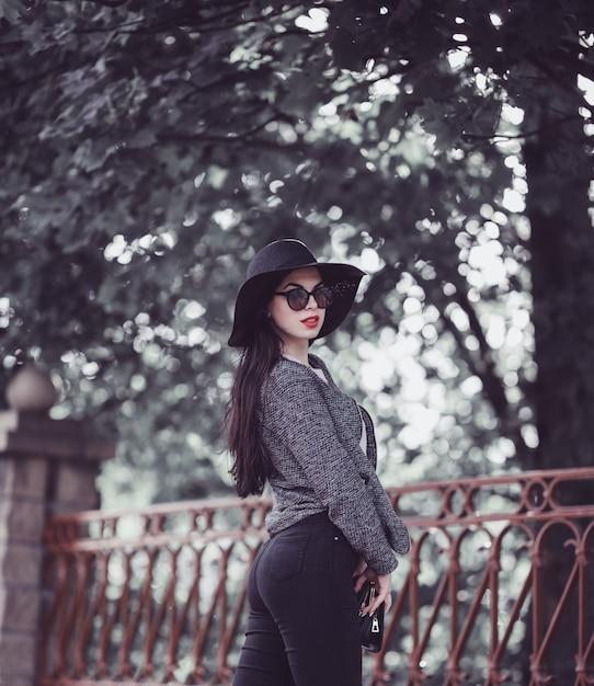 Leuke brunette met rode lippen in hoed en zonnebril die in stad stellen Premium Foto