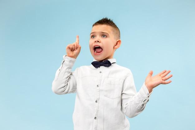Leuke elegante tienerjongen op blauwe achtergrond. emotionele uitdrukking Gratis Foto