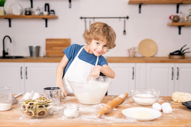 Leuke en grappige kleine jongen die in kom met bloem richt terwijl het ei gaat breken om deeg voor gebak te maken Premium Foto