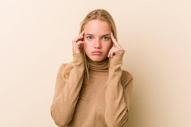 Leuke en natuurlijke tienervrouw gericht op een taak, waarbij wijsvingers hoofd houden. Premium Foto