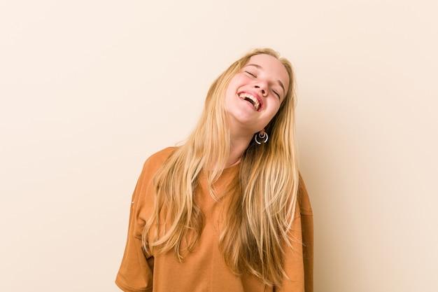 Leuke en natuurlijke tienervrouw ontspannen en gelukkig lachen, uitgerekte nek tonend tanden. Premium Foto