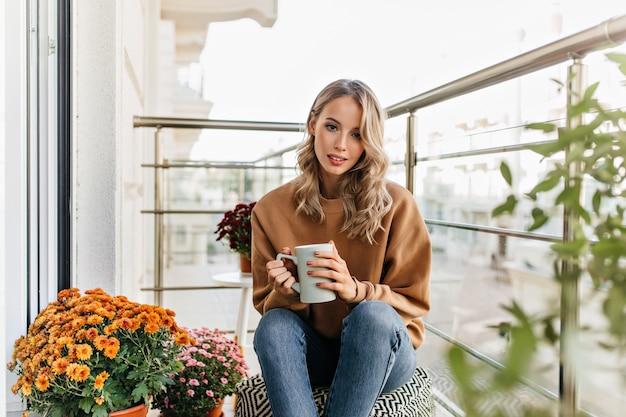 Leuke europese vrouw die thee drinkt op terras. portret van geïnteresseerd blond meisje dat van koffie geniet. Gratis Foto