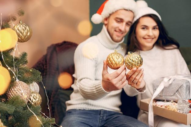 Leuke familie om thuis te zitten in de buurt van de kerstboom Gratis Foto