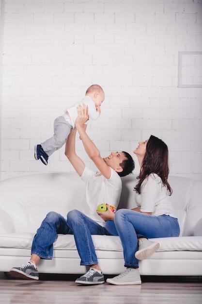 Leuke familie op studio achtergrond in licht, modern interieur binnenshuis. glimlachende jonge moeder en vader met kindzoon die samen stellen en op bank zitten. Premium Foto