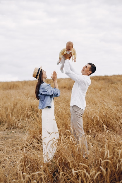 Leuke familie spelen in een herfst veld Gratis Foto