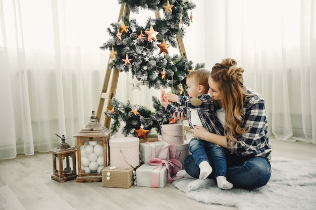 Leuke familiezitting dichtbij kerstboom Gratis Foto