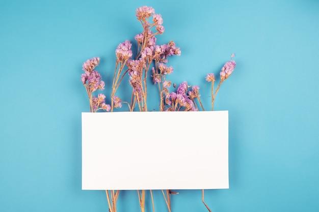 Leuke gedroogde violette statice bloem met witte kaart bovenop Premium Foto