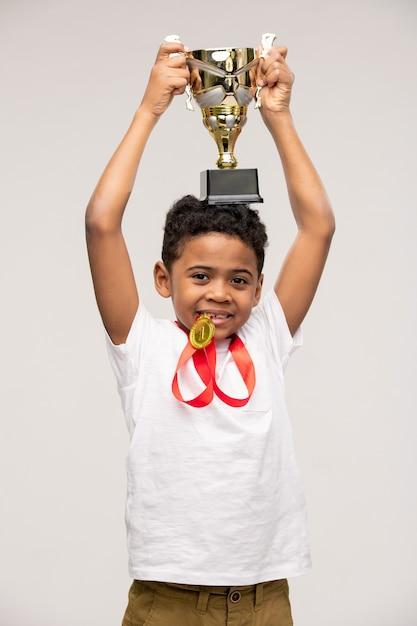 Leuke gelukkige kampioen van afrikaanse etniciteit die gouden medaille houdt door tanden en kop van winnaar op zijn hoofd houdt Premium Foto