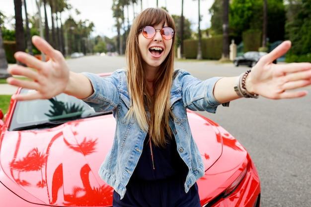 Leuke gelukkige vrouw in roze bril zelfportret maken in de buurt van geweldige rode converteerbare sportwagen in californië. Gratis Foto