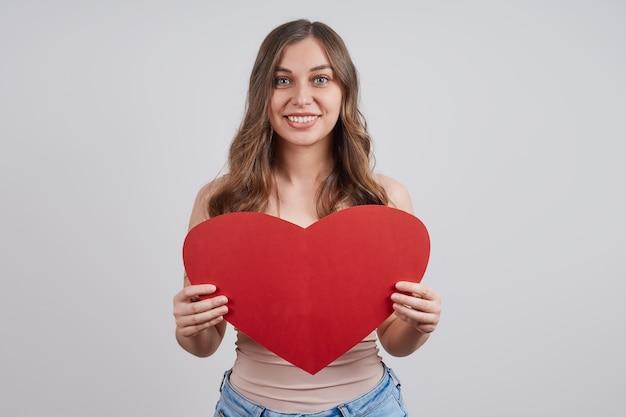 Leuke, gelukkige vrouw met een papieren hart, glimlachend. Premium Foto