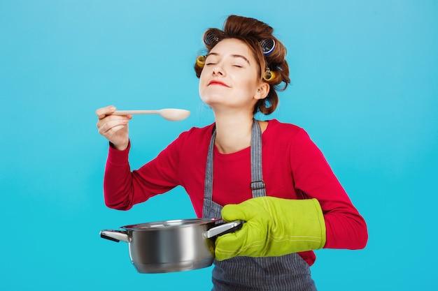 Leuke huisvrouw ruikt en proeft zelfgemaakte soep in de keuken Gratis Foto