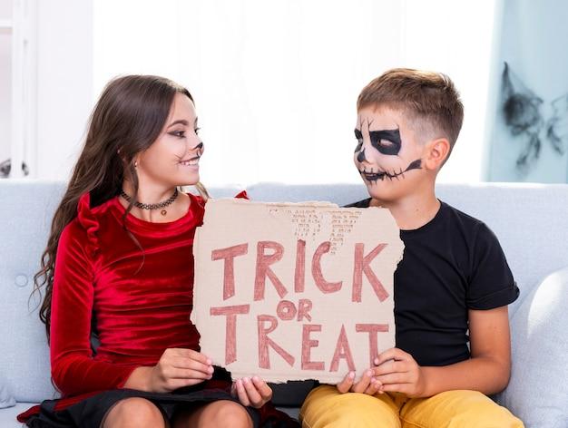 Leuke jonge broers die trick or treat-teken houden Gratis Foto