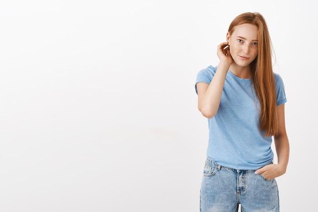 Leuke jonge europese roodharige vrouw met sproeten die haar achter het oor flikkeren, hand in de zak houden en met verlegen en ongemakkelijke uitdrukking staren Gratis Foto