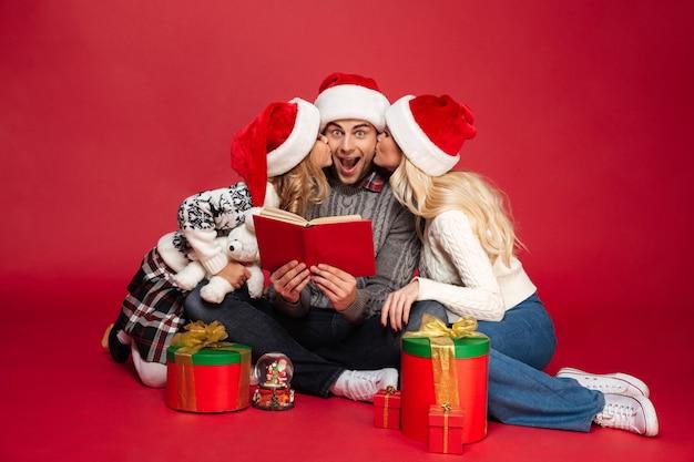 Leuke jonge familie die kerstmishoeden geïsoleerd zitten dragen Gratis Foto