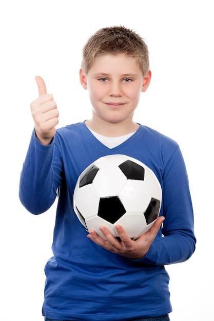 Leuke jonge jongen die een voetbalbal houdt Gratis Foto