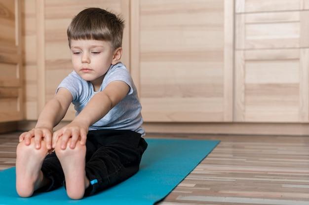 Leuke jonge jongen die op yogamat uitoefent Gratis Foto