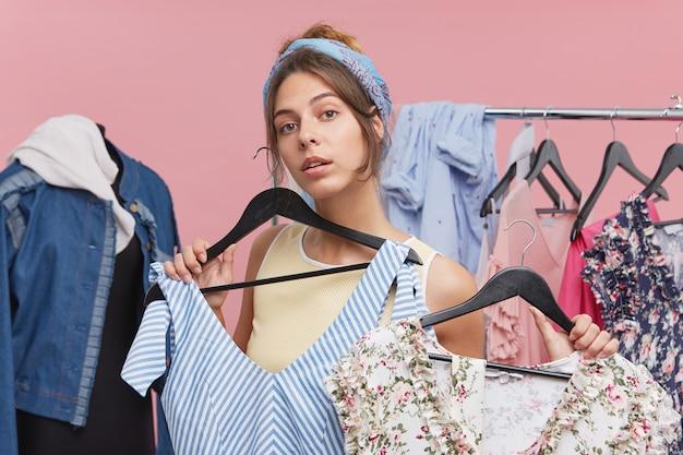 Leuke jonge vrouw die twee verschillende zomerjurken houdt die beslissen welke meer geschikt is om te dragen tijdens een wandeling. mensen, kleding, stijl en mode Gratis Foto