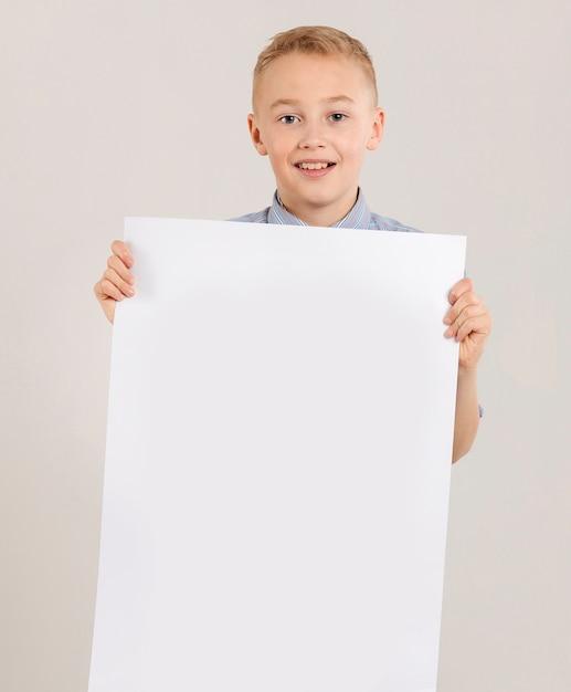 Leuke jongen die leeg document houdt Gratis Foto