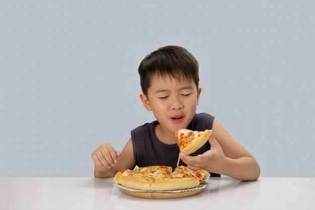 Leuke jongen die pizza eet die op blauwe achtergrond wordt geïsoleerd Premium Foto