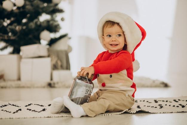 Leuke jongen in kerstmuts openen presenteert op kerstmis Gratis Foto