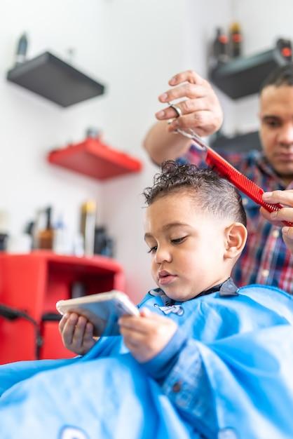 Leuke jongen krijgt een haar knippen in een kapper. schoonheid concept. Premium Foto