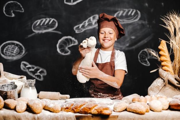 Leuke jongen met chef-kokhoed het koken Premium Foto