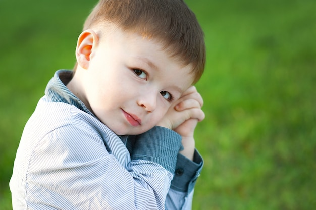 Leuke jongen zit op groen gras. hij wacht. kinderen blij Premium Foto