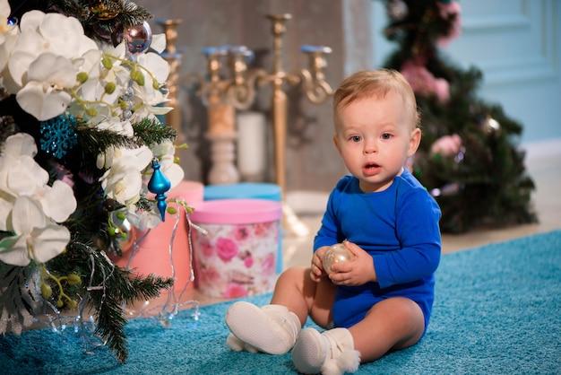 Leuke jongenszitting op het tapijt dichtbij kerstboom Premium Foto