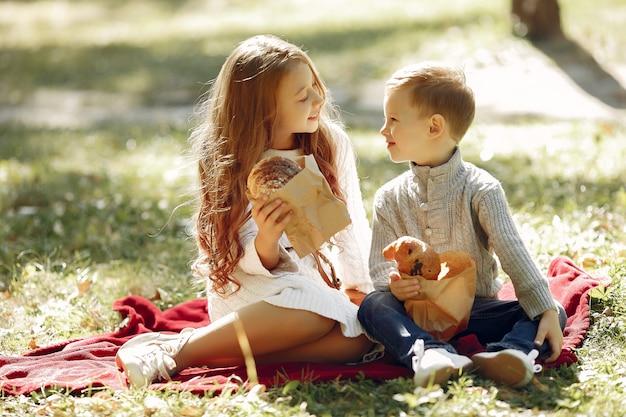 Leuke kleine kinderen die in een park met brood zitten Gratis Foto