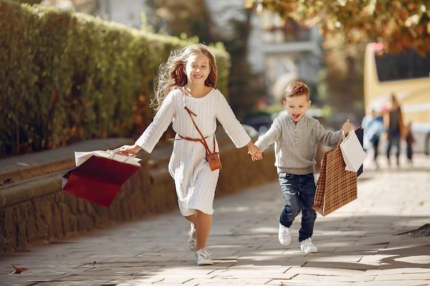 Leuke kleine kinderen met boodschappentas in een stad Gratis Foto