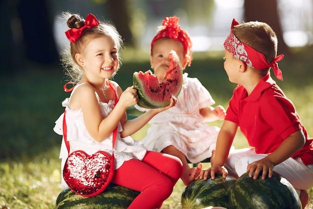 Leuke kleine kinderen met watermeloenen in een park Gratis Foto