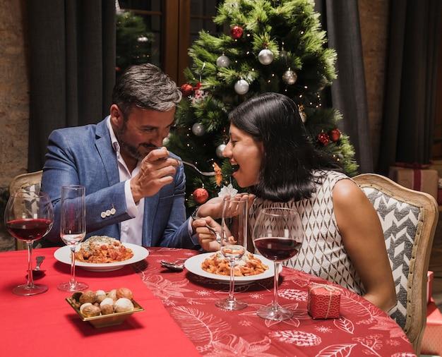 Leuke man en vrouw die kerstmisdiner hebben Gratis Foto