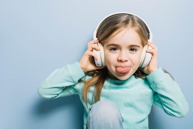 Leuke meisje het luisteren muziek op hoofdtelefoon die haar tong uitsteekt Gratis Foto