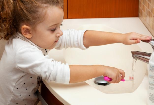 Leuke meisje schoonmakende tand met borstel. Premium Foto
