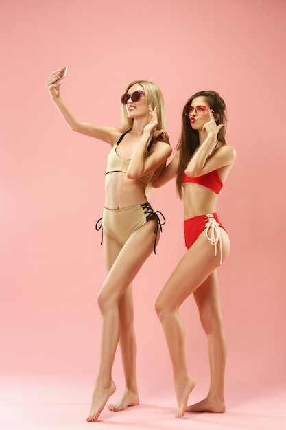 Leuke meisjes in zwembroek poseren en foto selfie maken op mobiele telefoon in studio. Gratis Foto