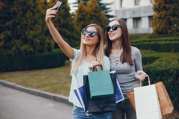 Leuke meisjes met boodschappentas in een stad Gratis Foto