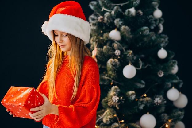 Leuke meisjestiener in rode kerstmuts door kerstboom Gratis Foto