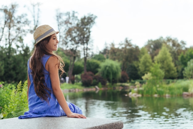 Leuke meisjeszitting door het meer van erachter Gratis Foto