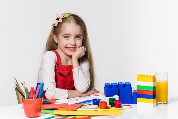 Leuke meisjetekening met verf en penseel thuis Gratis Foto