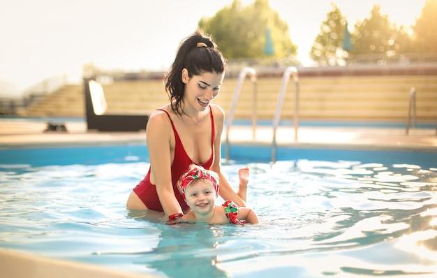 Leuke moeder die haar dochter leert hoe te zwemmen Premium Foto