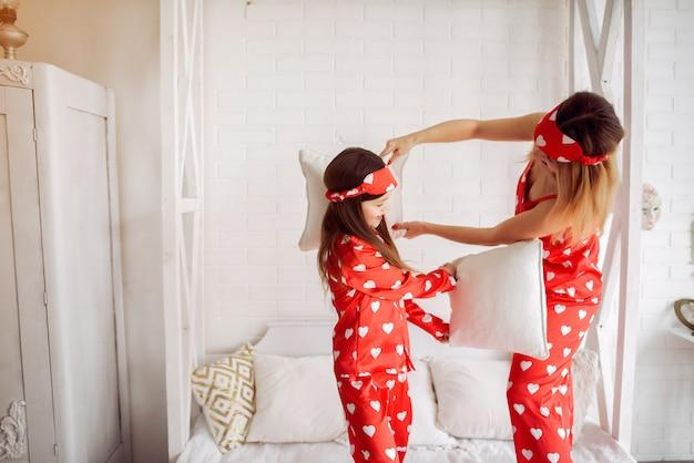 Leuke moeder en dochter thuis in pyjama's Gratis Foto