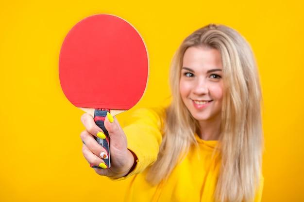 Leuke mooie jonge blonde vrouw in casual gele sportieve kleding spelen pingpong, met een bal en racket. Premium Foto