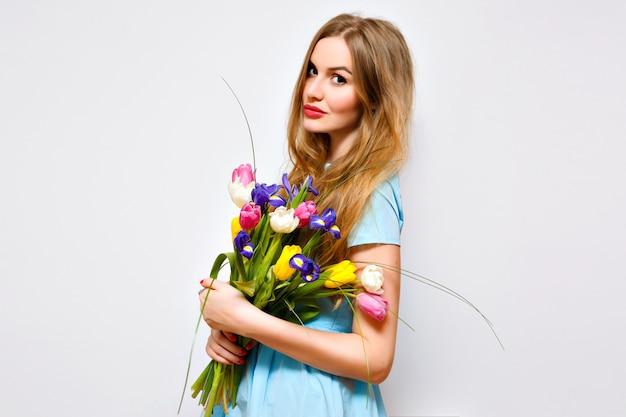 Leuke mooie vrouw poseren met zacht pastel lenteboeket, witte muur, huidige vakantie, vintage jurk, lange blonde haren en natuurlijke make-up. Gratis Foto