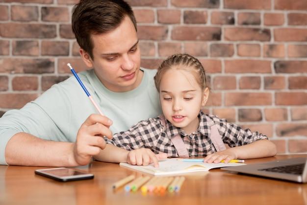 Leuke nieuwsgierige dochter met gevlochten haren zittend op vaders knieën aan tafel en beschrijft tekening aan papa terwijl ze samen huiswerk doen Premium Foto