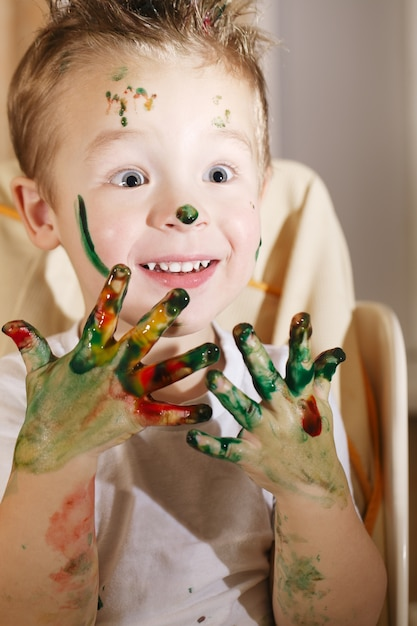 Leuke opgewonden jongen met handen vol vingerverf Premium Foto
