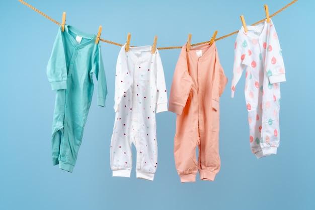 Leuke peuter kleurrijke kleding hangt aan een touw Premium Foto