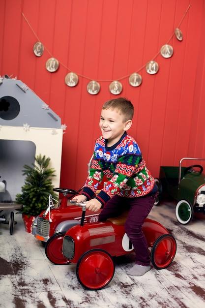 Leuke peuter speelt met speelgoed rode auto's. rijdt op een speelgoedmachine met typemachine. gelukkige jeugd. Premium Foto